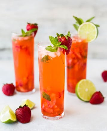 Image of 3 bright red fruity cocktails with strawberry and lime garnishes.
